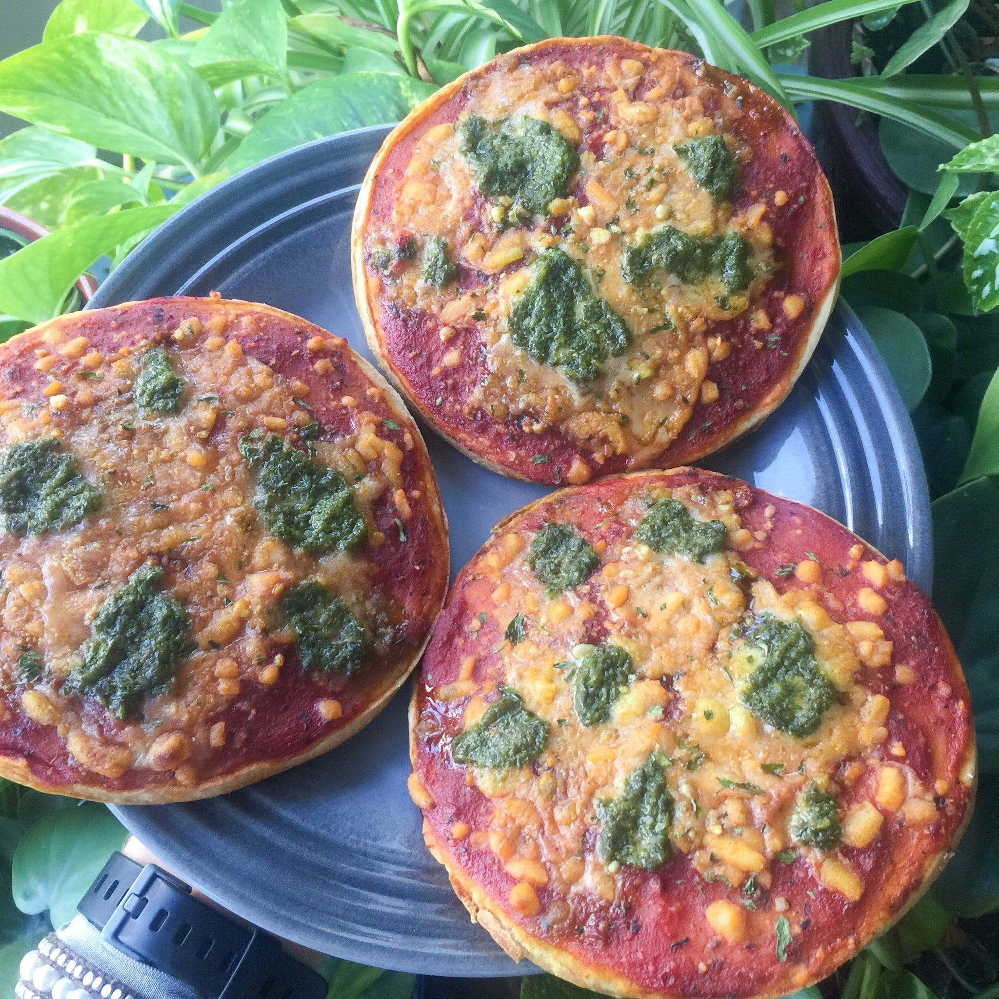 three mini pesto and cheese vegan pizzas