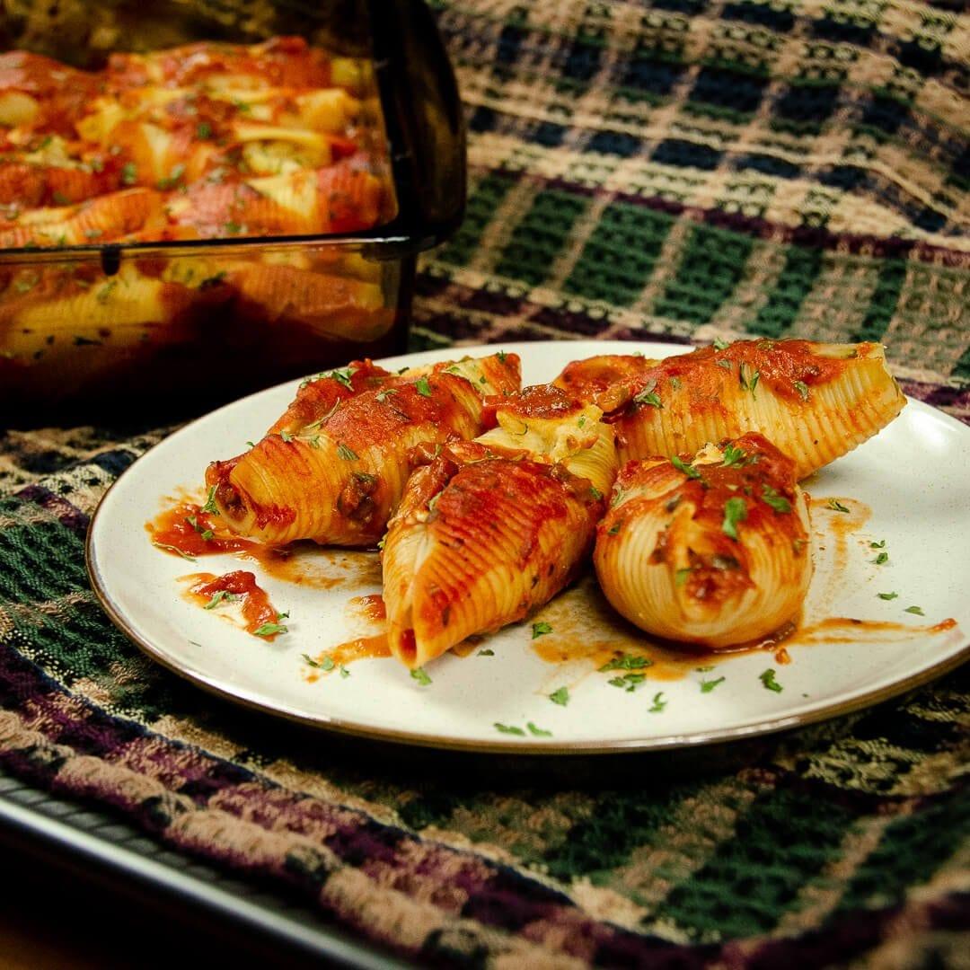 vegan ricotta stuffed shells recipe hero plate and casserole